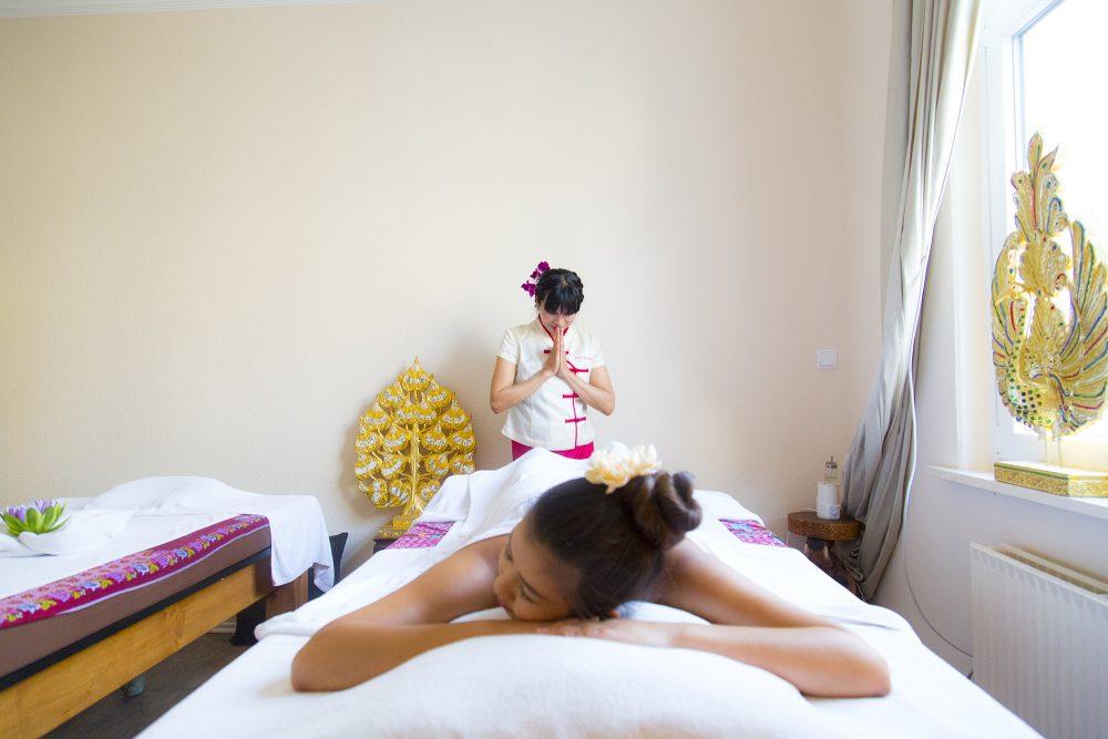 Massagebeginn, Masseurin hinter Kundin auf der Massageliege